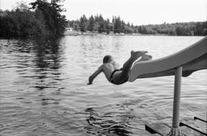 garçon plongeant sur un lac